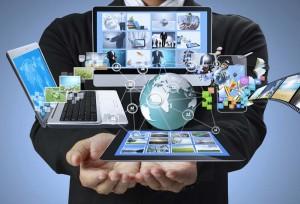 Mężczyzna trzymający w objęciach laptopa, tablet, smarfona i inne multimedia